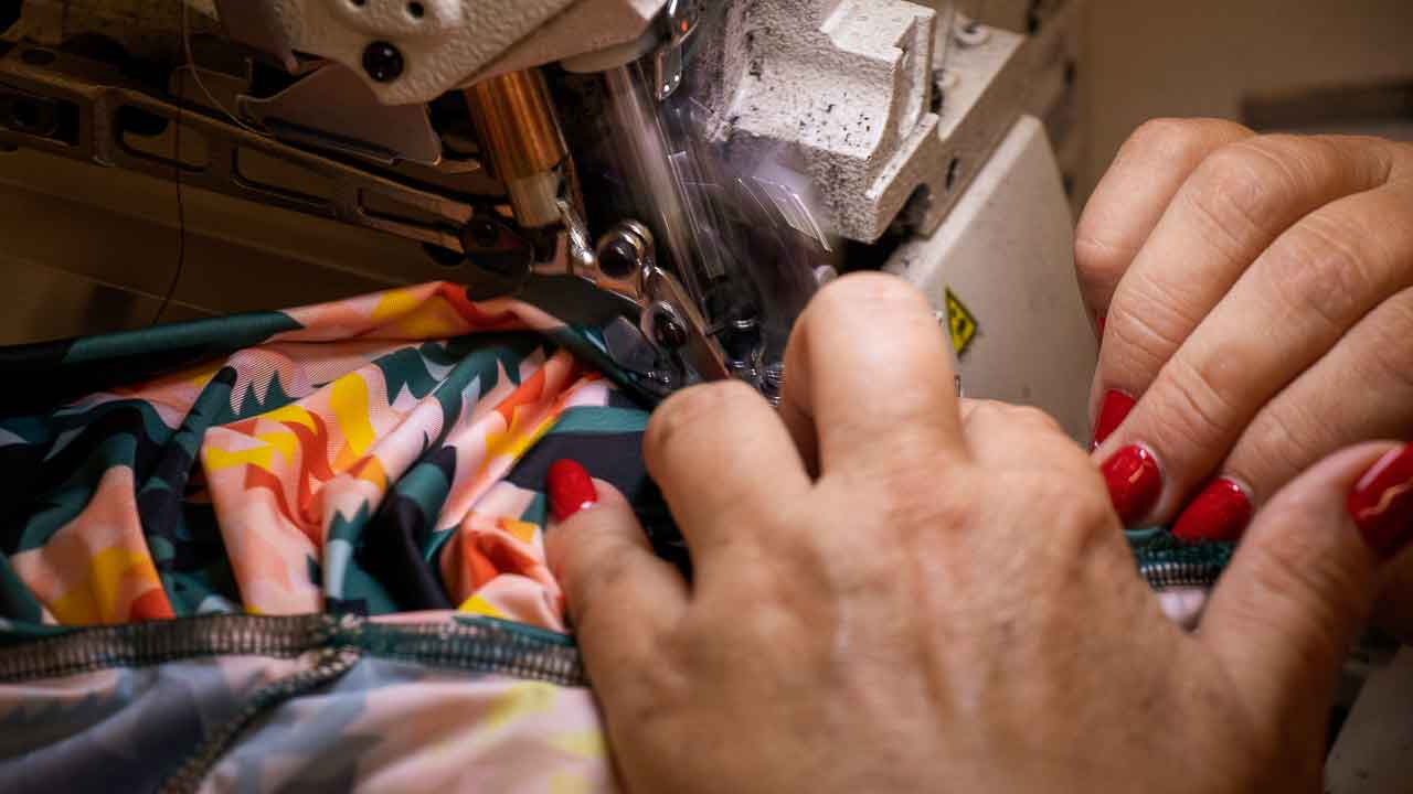 Machinist with bright red finger nails sewing the Asmuss Geo. Rose T-shirt