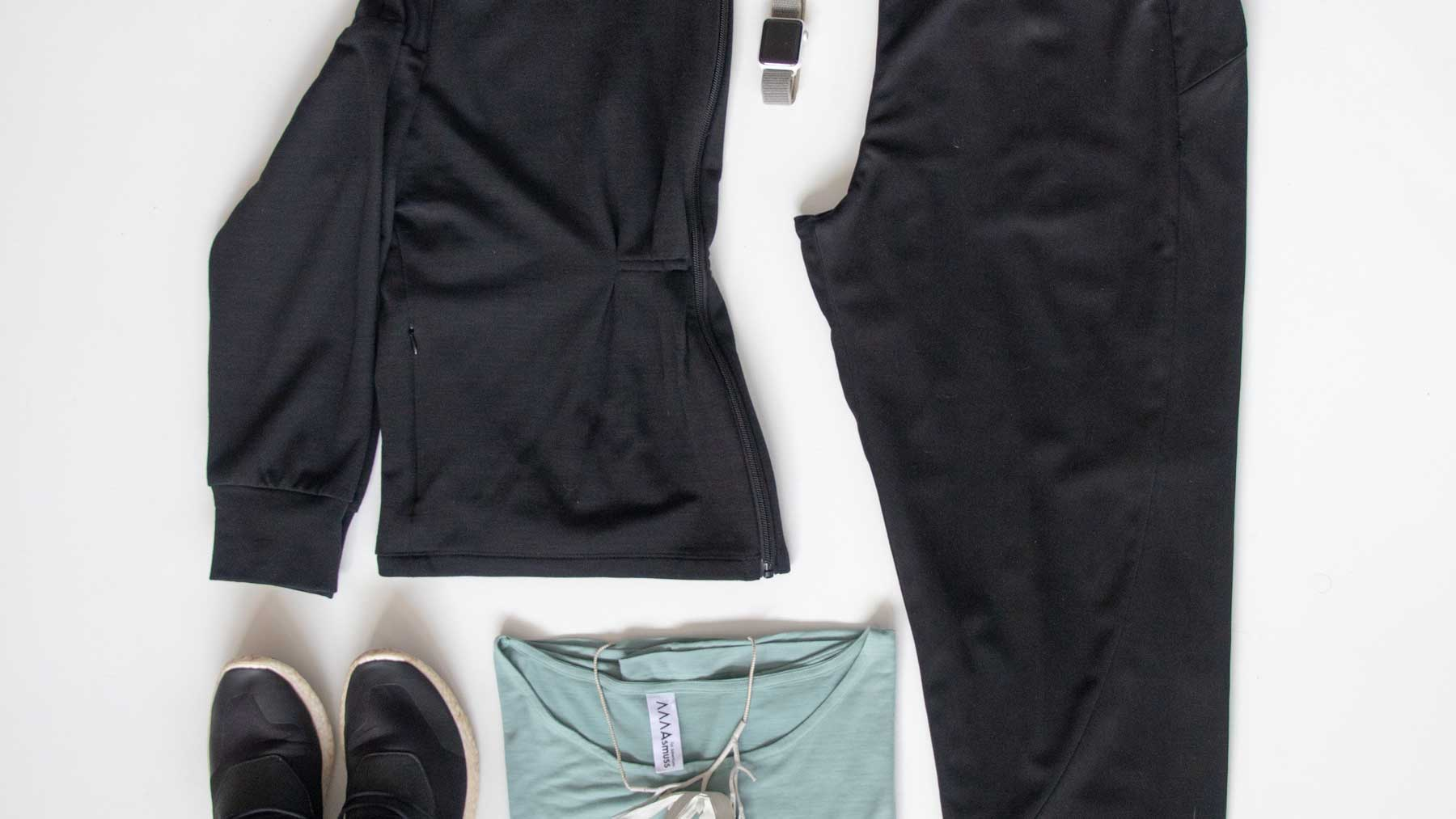 Flat lay image of Asmuss clothing to pack for travel to Fogo Island including the Asmuss Pleated Zip Through Sweat, Asmuss Panelled Trousers and Asmuss A-line T-shirt in sea green along with accessories to finish a great travel outfit off