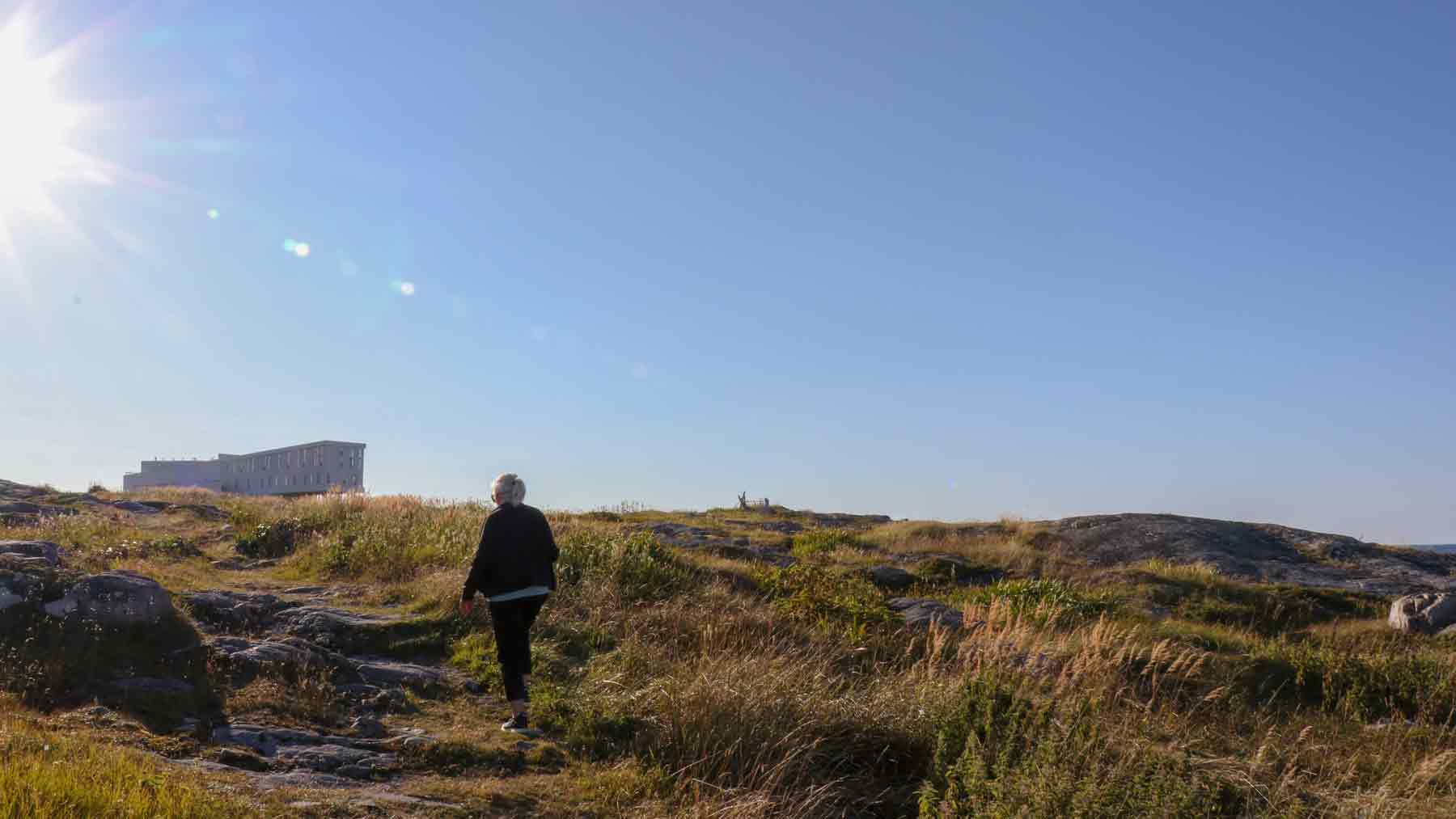 The Asmuss founder's Mum walking up a hill into the sun on Fogo Island