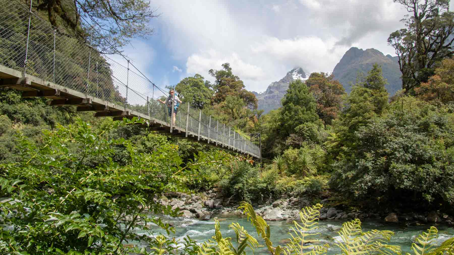 One of many swing bridges on the Hollyford Track.  The Asmuss founders sister is crossing the swing bridge wearing Asmuss luxury travel clothing designs, Hollyford Track, Fiordland, New Zealand