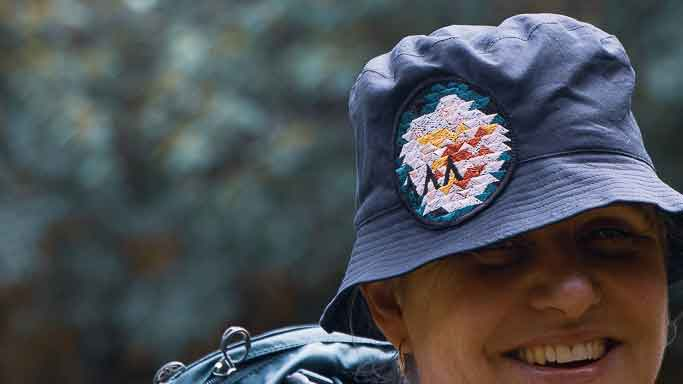 Fiona, an Asmuss co-founder, wearing a sample of the  Asmuss bucket hat with Evelyn rose inspired embroidered badge with a backpack on.  She is smiling rather than grimacing.