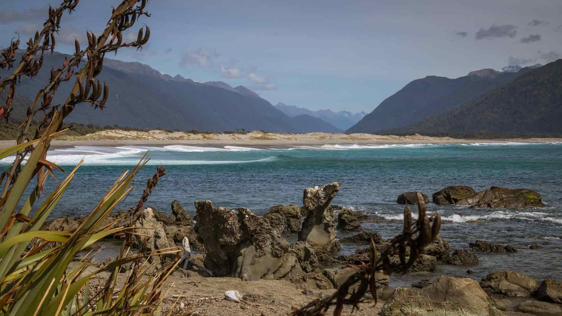 View from Martins Bay, with flax, sea and sand hills in the foreground,  up the Hollyford Valley, Fiordland, New Zealand taken by Asmuss founder Fiona. Walking the Hollyford Track was a great test of the Asmuss luxury stylish sustainable travel clothing