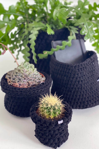 Group of crocheted pot plant covers and baskets made from waste fabric