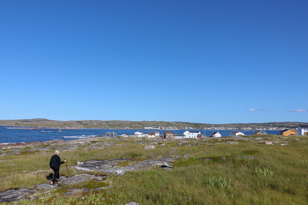White haired women walking on Fogo Island with cottages in the distance on the coast