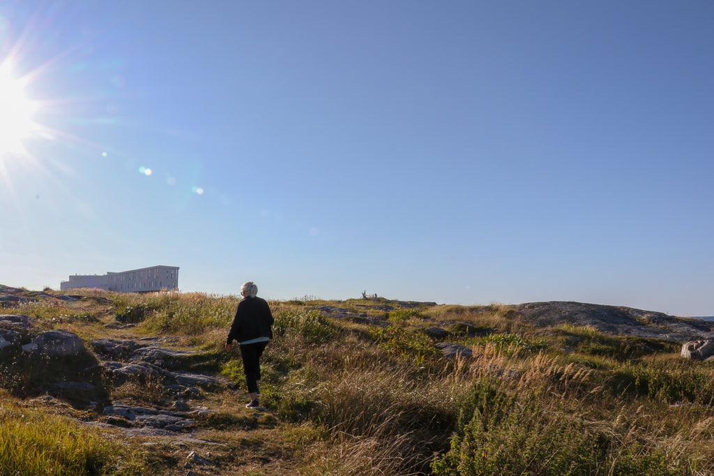 White haired woman walking up a hill into the sun on Fogo Island
