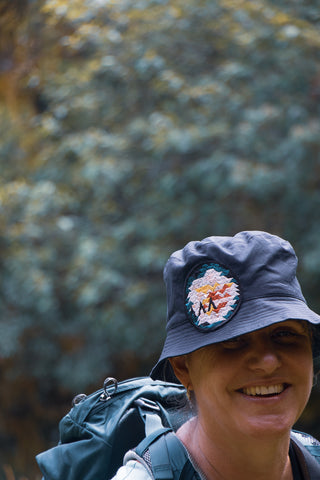 Fiona, an Asmuss co-founders, wearing a sample of the  Asmuss bucket hat with Evelyn rose inspired embroidered badge with a backpack on.  She is smiling rather than grimacing.