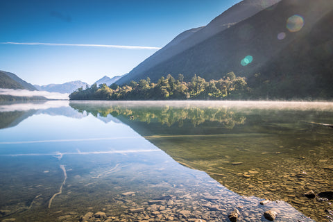The hills and sky reflected on the glasslike surface of Lake Alabaster, Fiordland, New Zealand. Taken by Asmuss founder Fiona