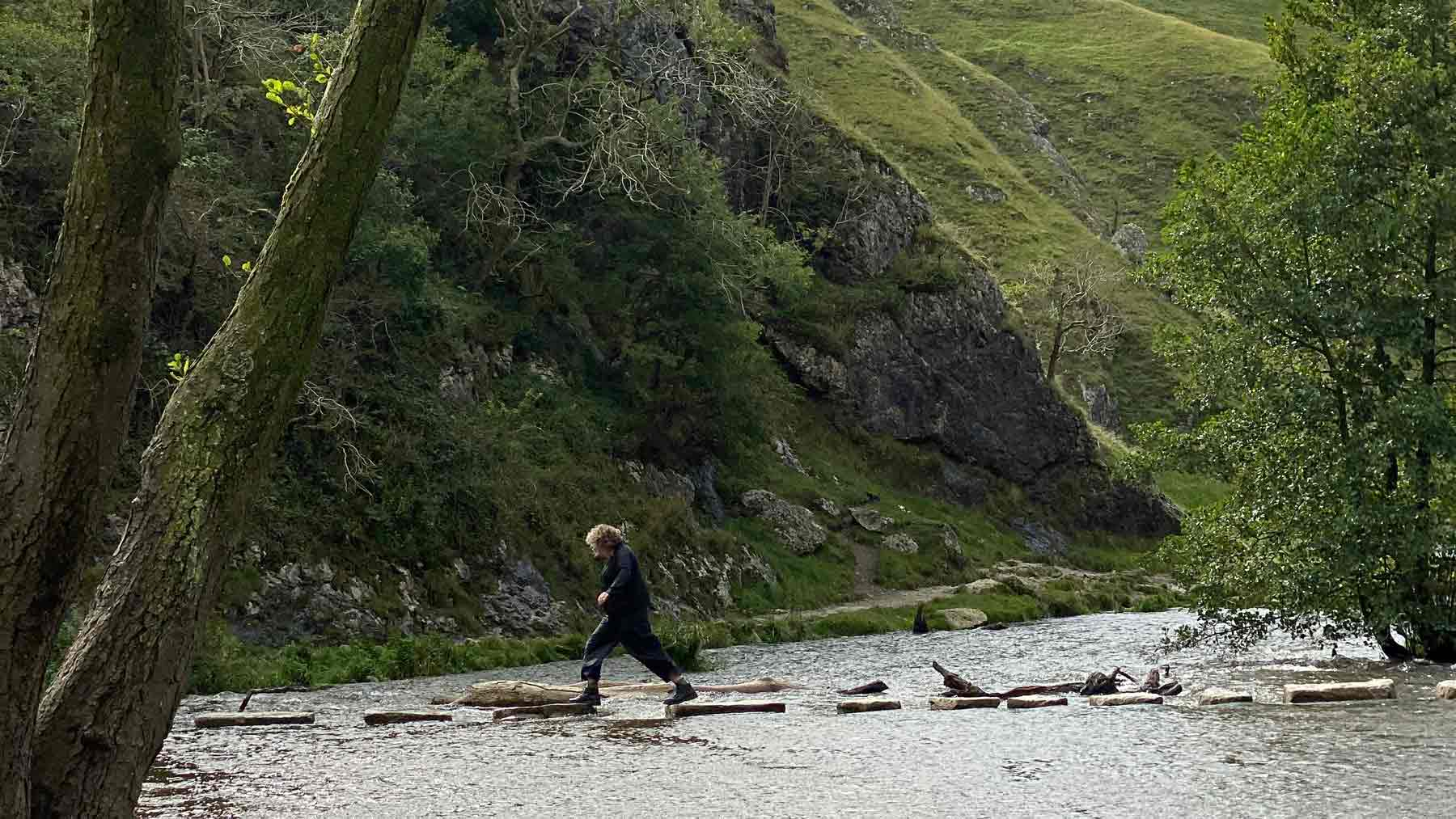 Clare wearing Asmuss jumping across the Dovedale Stepping Stones in the Peak District