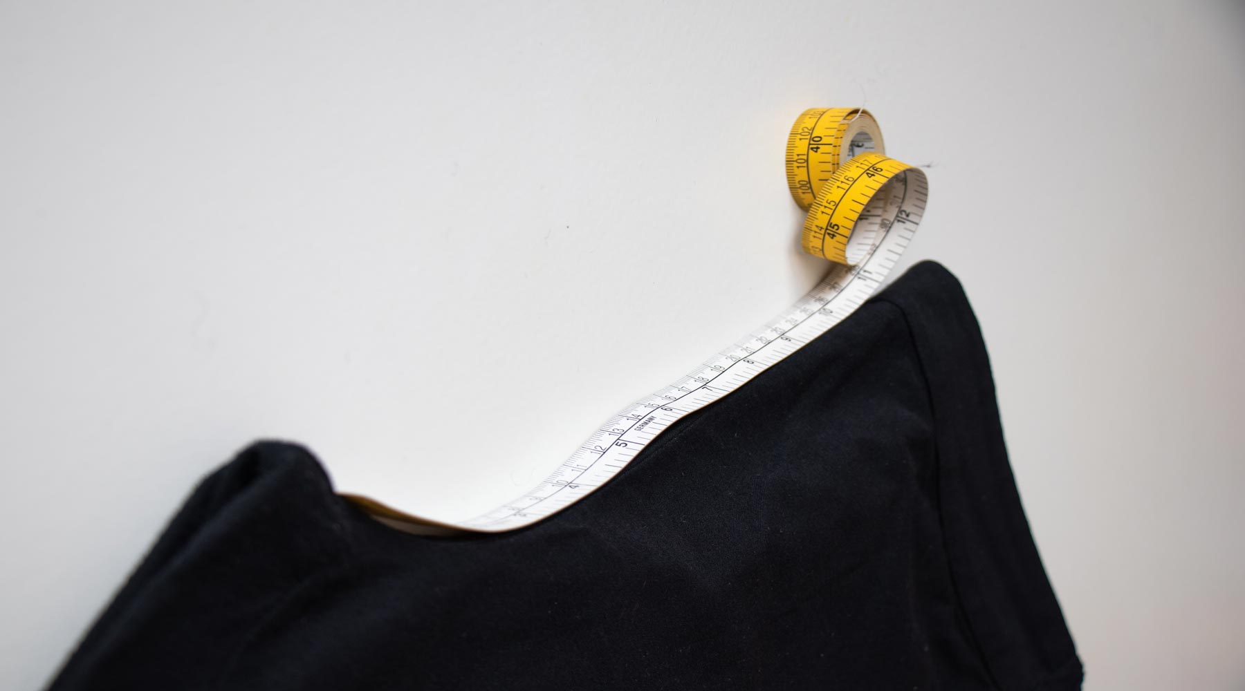 Measuring tape showing how to measure the front rise of a pair of trousers