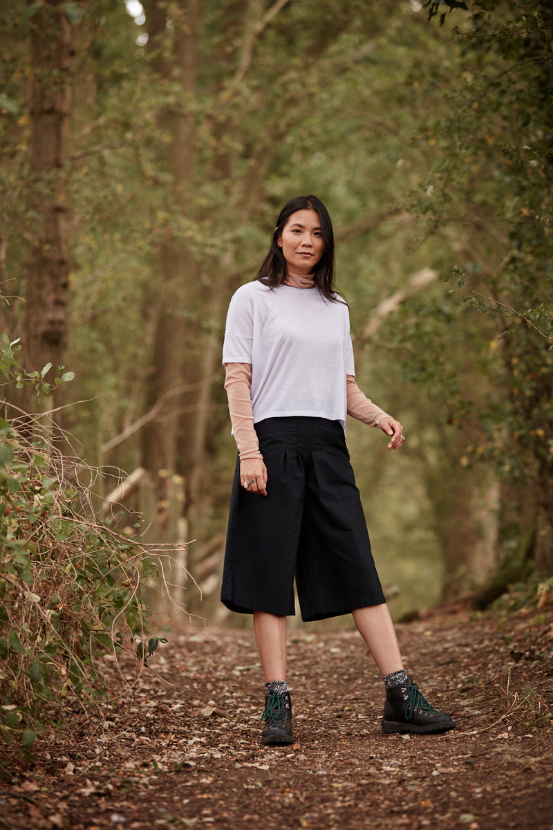 Woman wearing the Asmuss Boxy Cropped T-shirt in White in the forest.  A great luxury basic that is stylish and sustainable.