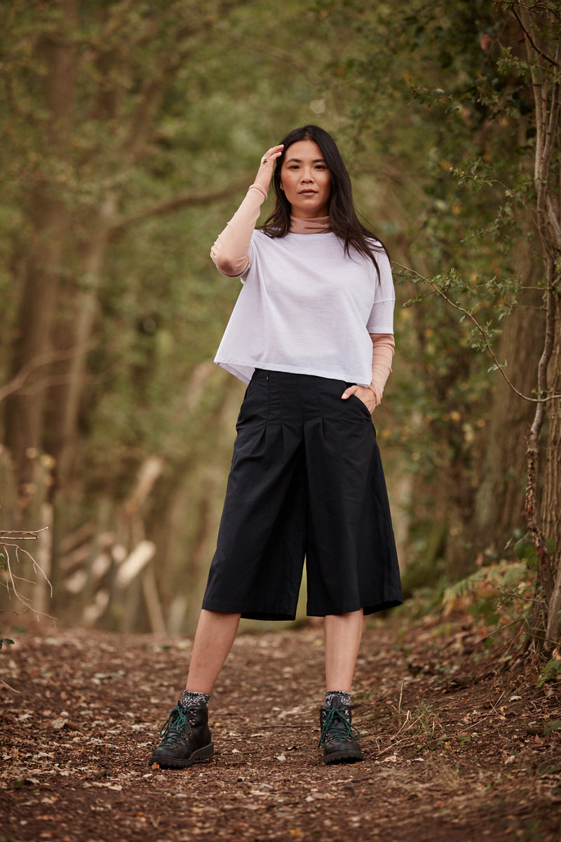 Woman wearing the Asmuss Boxy Cropped T-shirt in White.  Stylish sustainable performance womenswear for travel or everyday
