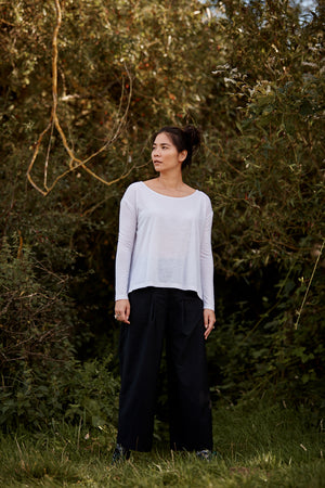 Woman wearing Asmuss Aline Long Sleeve T-shirt in White.  It is temperature regulating so an essential garment in a travel wardrobe