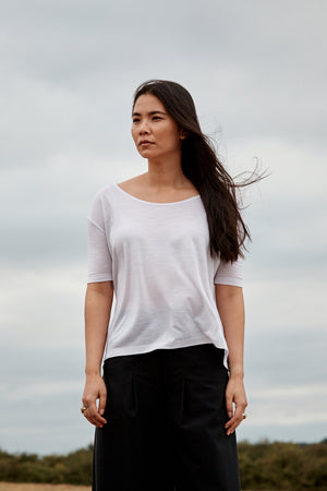 Woman wearing the Asmuss Aline T-shirt in White.  Luxurious and technically innovative fabric to take you on any adventure or travels
