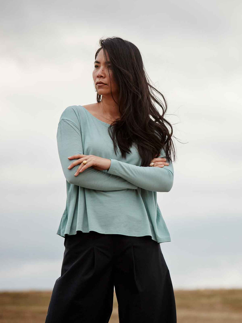 A modern woman standing strong in the beautifully falling Asmuss Long Sleeve A-line T-shirt in Sea Green. An elevated for all your everyday adventures it is made from soft wool blended with 37.5 Technology to help regulate your body temperature