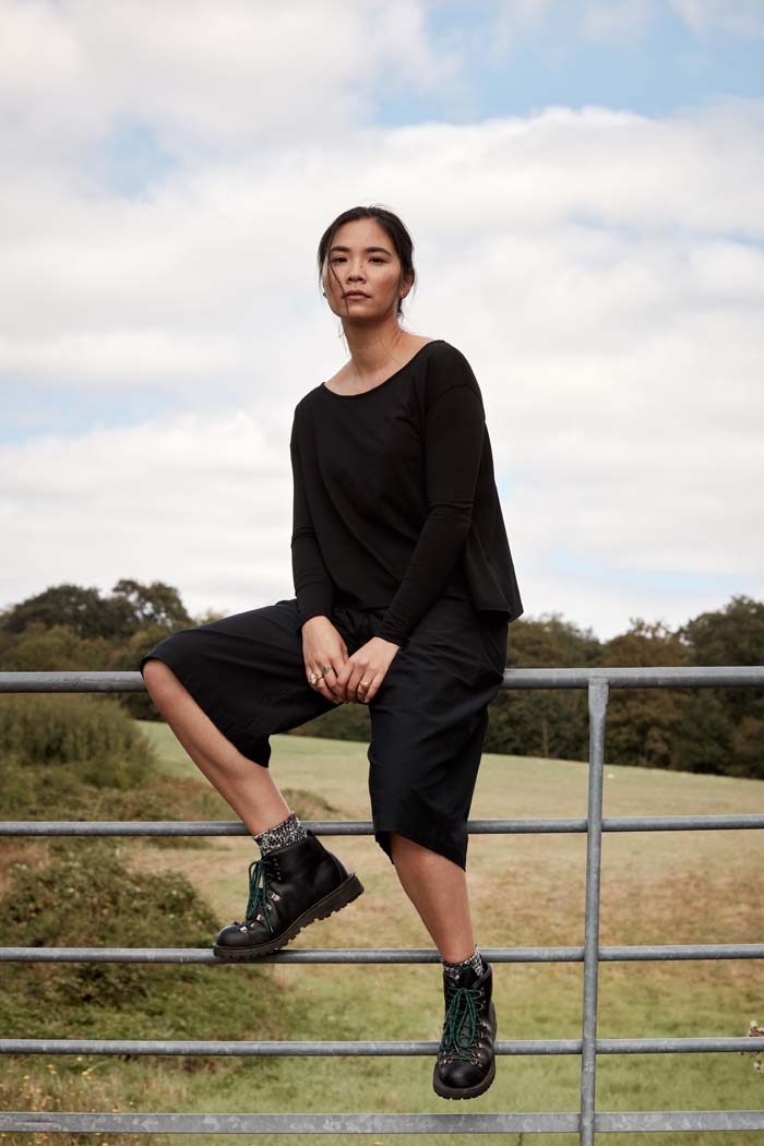 Woman sitting on a farm gate wearing the Asmuss Pleated Culottes in Black. The cropped wide leg culottes are perfect elevated essentials for everyday. Great sustainable culottes for the outdoors, travel or everyday adventures with stretch and water resistance in a sustainable fabric.
