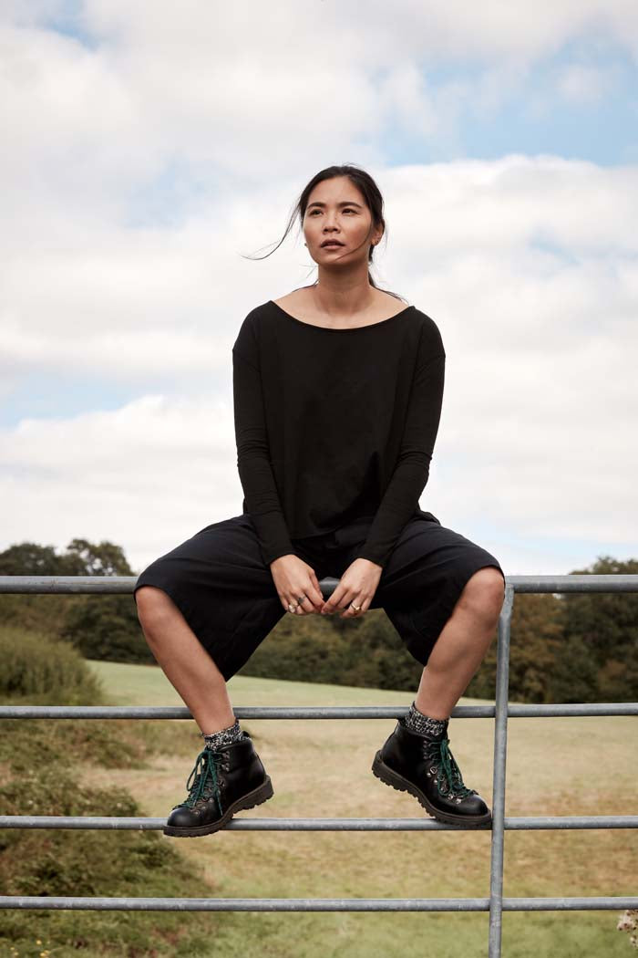 Woman wearing the elevated essential Asmuss A-line Long Sleeve T-shirt in Black. The perfect everyday and travel top as it adapts to your own microclimate through clever built in technology