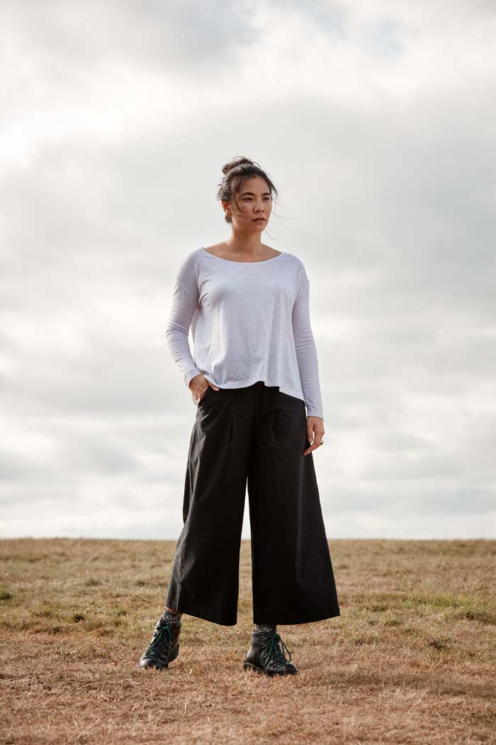 Woman, standing in a field, wearing the Asmuss Wide Leg Trouser in black. Made in the UK in small batches from a sustainable fabric with built in stretch and water resistance. Stylish, sustainable trousers that are elevated by the design details including hidden zip pocket and high elasticated waist for convenience and comfort. Perfect for all your everyday or travel adventures.