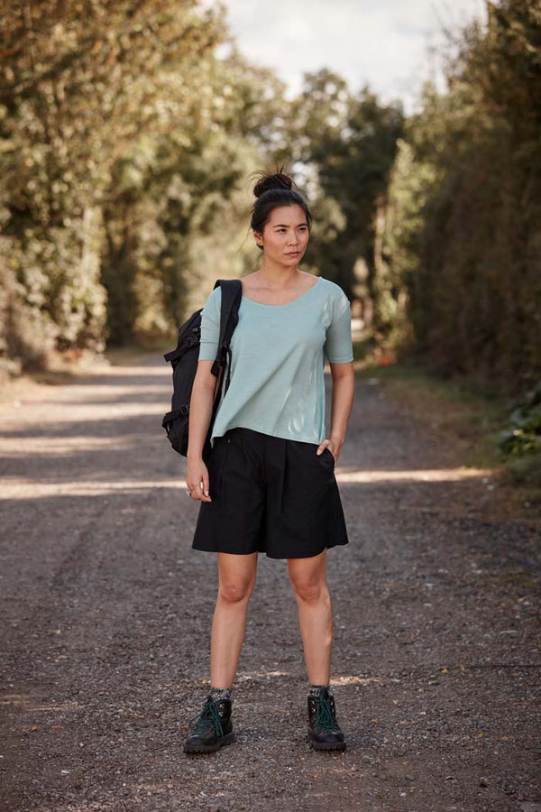 Woman wearing the Asmuss Pleated Shorts in Black on walk down a country track. Made from a sustainable castor bean based fabric that has built in stretch and water resistance they feature side pockets and a hidden zip pocket in the pleats. Stylish, sustainable lifestyle womenswear for your everyday and travel adventures. An essential elevated beyond activewear.
