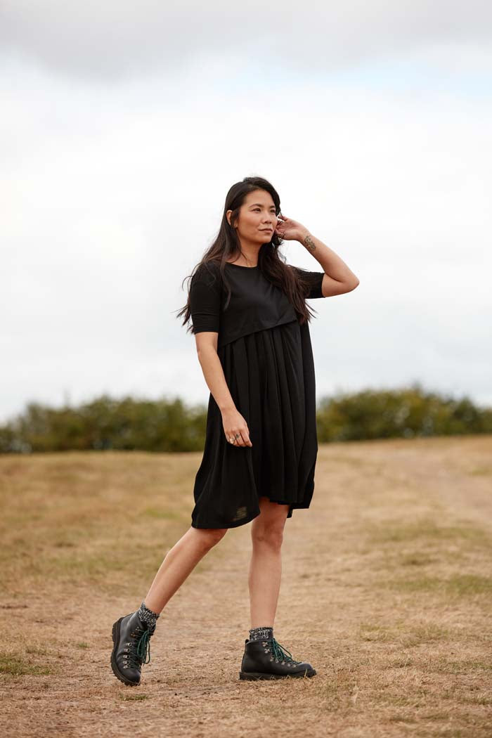 Woman wearing the Asmuss Asymmetric Pleat Dress in Black for a countryside walk. Look stylish while being functional and comfortable an ideal everyday essential that has built in temperature regulating 37.5 Technology.
