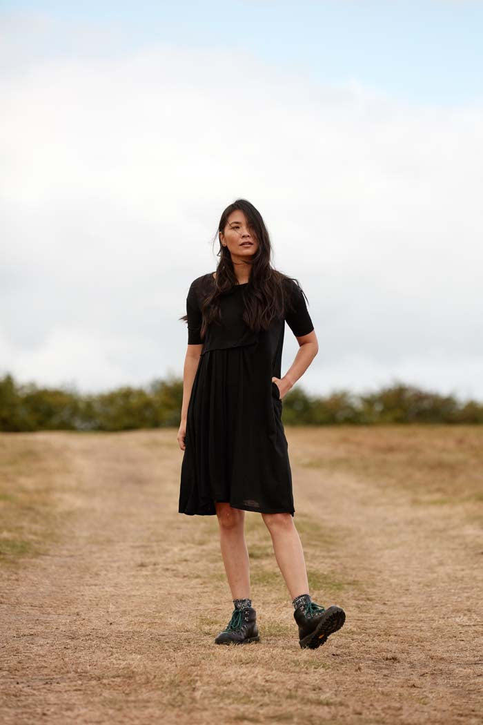 Woman wearing the Asmuss Asymmetric Pleat Dress in Black. A little black dress that can take you from the office, to gallery, restaurant or any other everyday adventure.
