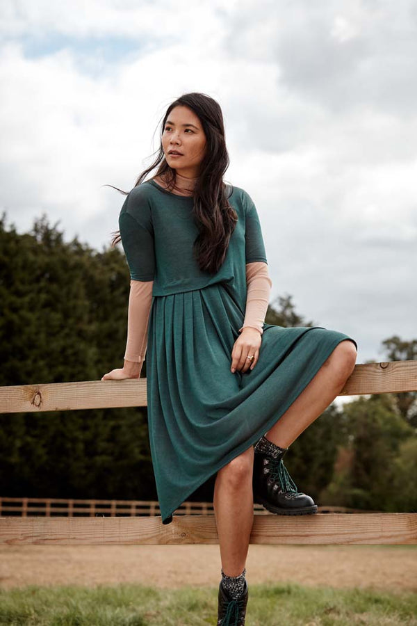 Woman wearing the Asmuss Asymmetric Pleat Dress in Pine Green. Slim arms, loose fitting body with pleat detail and pocket it makes a great dress for your everyday adventures. Made from a blend of recycled polyester and Tencel a great sustainable fabric. A stylish, sustainable addition to the modern woman's wardrobe.