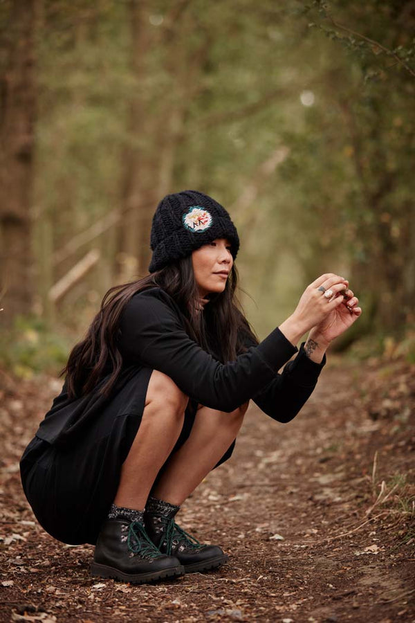 Woman in the woods wearing the Asmuss Handknitted Beanie in Black for when you need that extra warmth on your everyday adventures but still want to look stylish