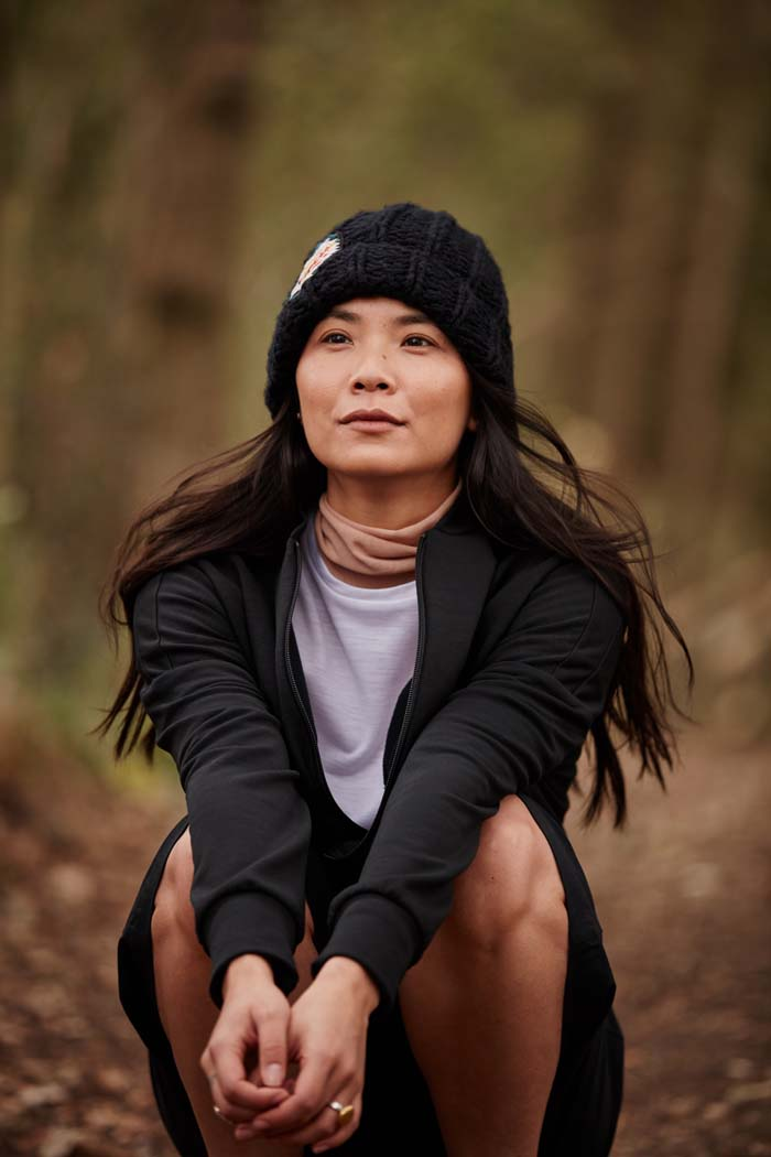 Woman in the woods wearing the Asmuss Handknitted Beanie in Black for when you need that extra warmth on your everyday adventures but still want to look stylish. Sustainably made from upcycled yarn.