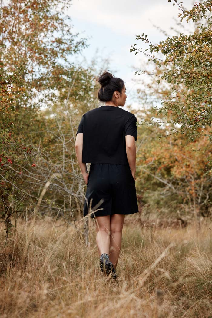 Woman wearing the Asmuss Pleated Shorts in Black. Made from a sustainable castor bean based fabric that has built in stretch and water resistance they feature side pockets and a hidden zip pocket in the pleats. Stylish, sustainable lifestyle womenswear for your everyday and travel adventures. An essential elevated beyond activewear.