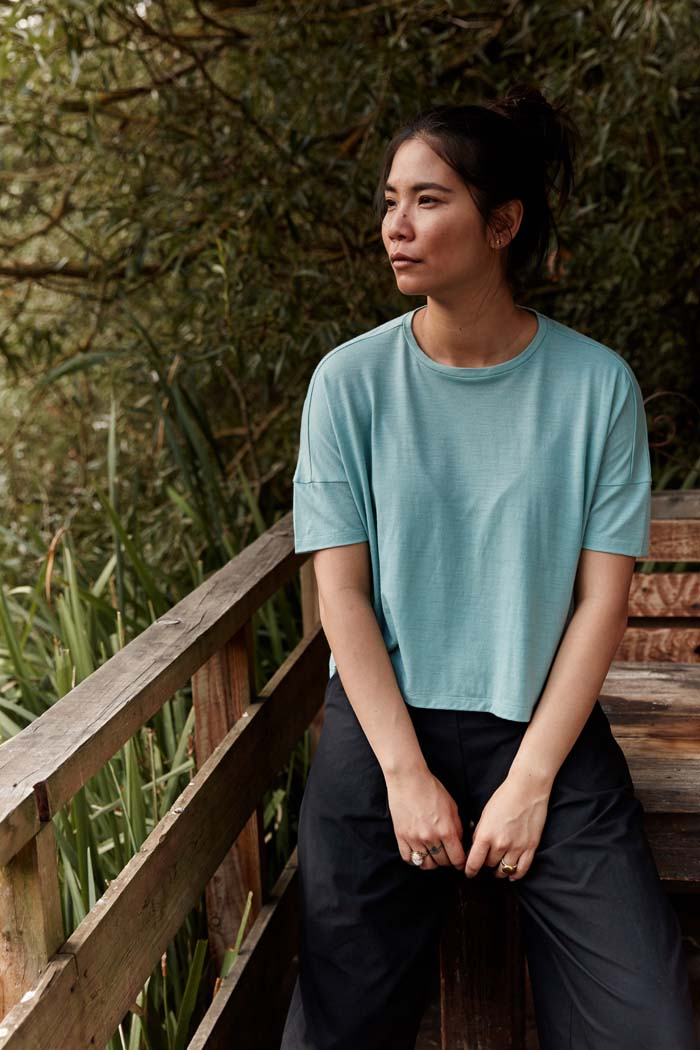 Woman sitting on a wooden bench in the countryside wearing the Asmuss Boxy Cropped T-shirt in Sea Green. Made in the UK from a blend of wool and 37.5 Technology to help keep you at the ideal body temperature. One of the best elevated essentials for the modern woman's everyday adventures.