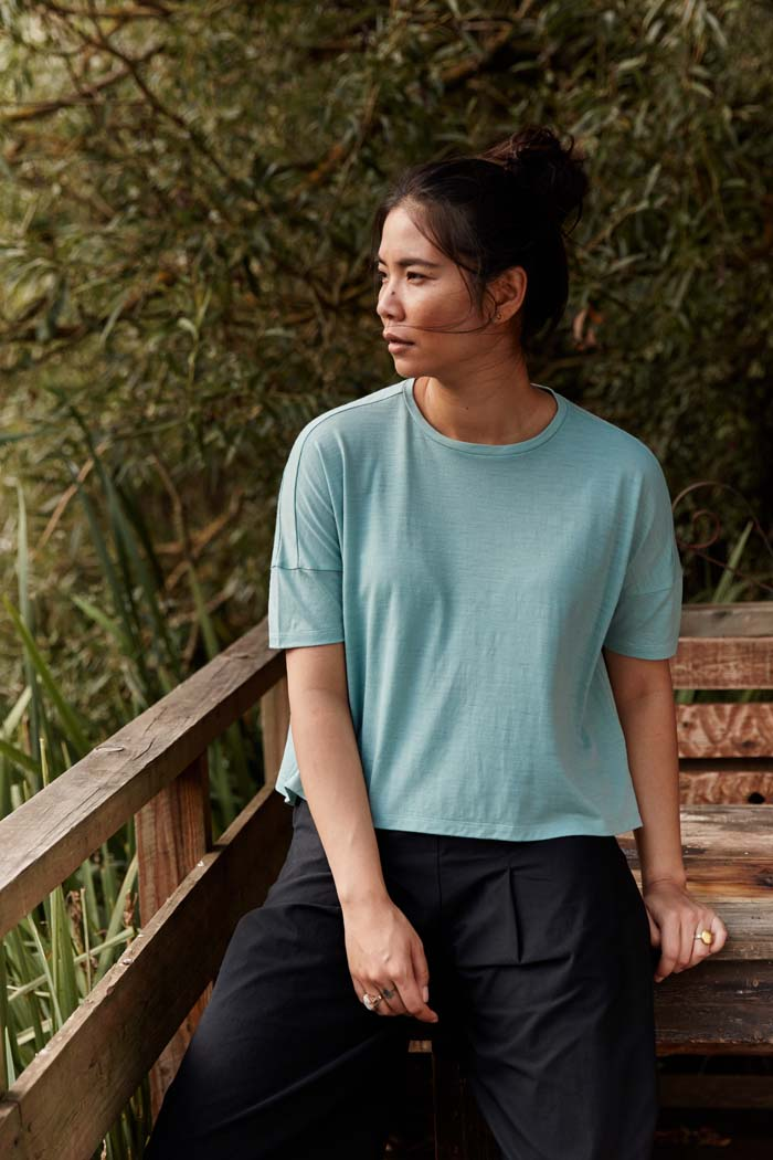 Woman leaning on a wooden bench wearing the Asmuss Boxy Cropped T-shirt in Sea Green. Innovative temperature regulating 37.5 Technology helps keep you feeling dry and comfortable all day long. It is a perfect elevated t-shirt with clever detailing to add to its style.
