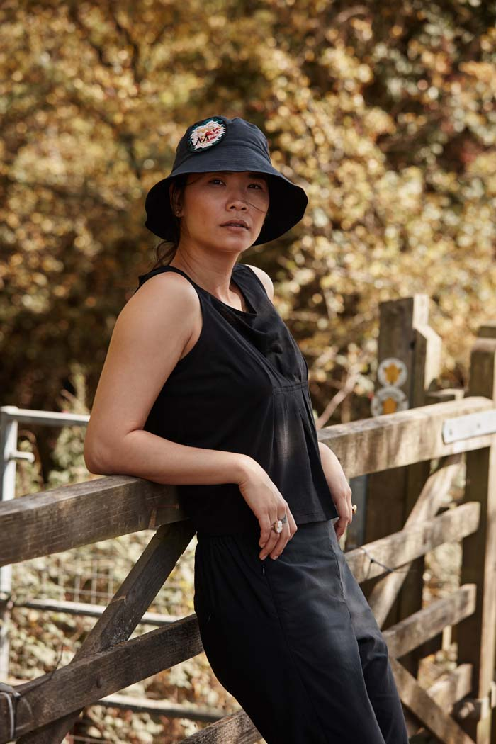 Woman leading on her elbows relaxing during a walk in the countryside wearing the Asmuss Wide Brim Bucket Hat in black with rose embroidery badge. Made from water resistant sustainable fabric it is the perfect sun hat to keep the sun off your face but still look good and keep the rain off too.