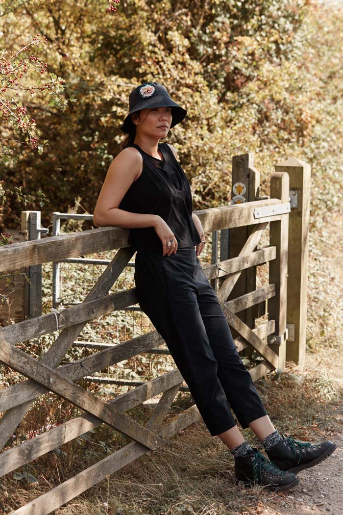 Woman leaning on a wooden gate while out for a walk wearing the Asmuss Pleated Tank in Black. Made in small batches in the UK from a luxury wool blended with temperature regulating 37.5 Technology. A perfect summer elevated essential for all your everyday adventures.