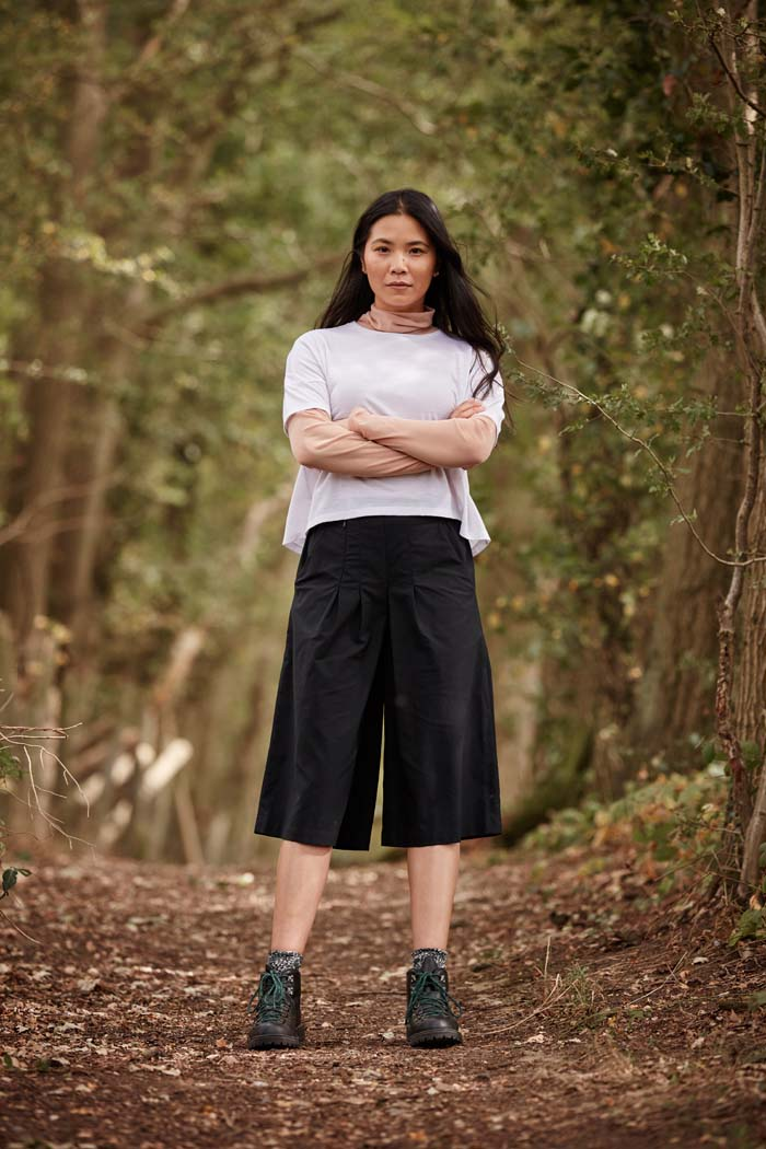 Woman with arms crossed wearing the Asmuss Pleated Culottes in Black while standing in a forest. The cropped wide leg culottes are perfect elevated essentials for everyday. Great sustainable culottes for the outdoors, travel or everyday adventures with stretch and water resistance in a sustainable fabric..
