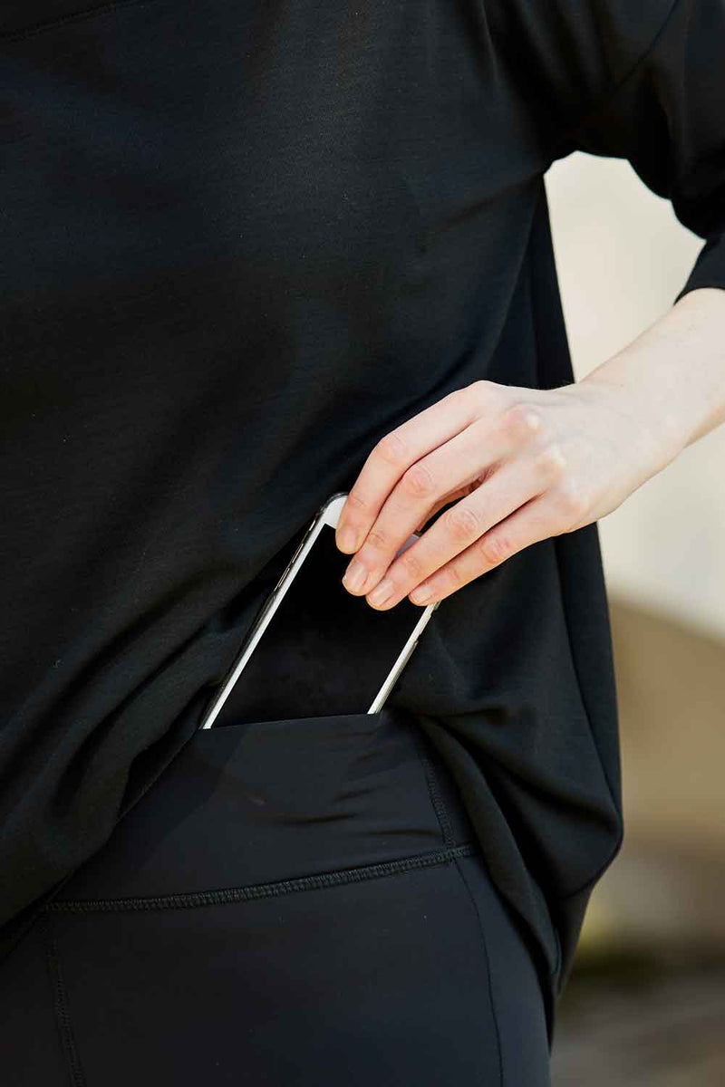 Showing how the kangaroo pocket in the waistband of the Asmuss Twisted Leggings holds a phone. The high waisted Asmuss Twisted Leggings with zip detail on lower front leg, pocket in front waistband and drawstring to keep them snug. Made in the UK from recycled nylon and elastane for 4 way stretch. Sustainable activewear that looks great on for all your everyday adventures including lazing on the couch or out running.