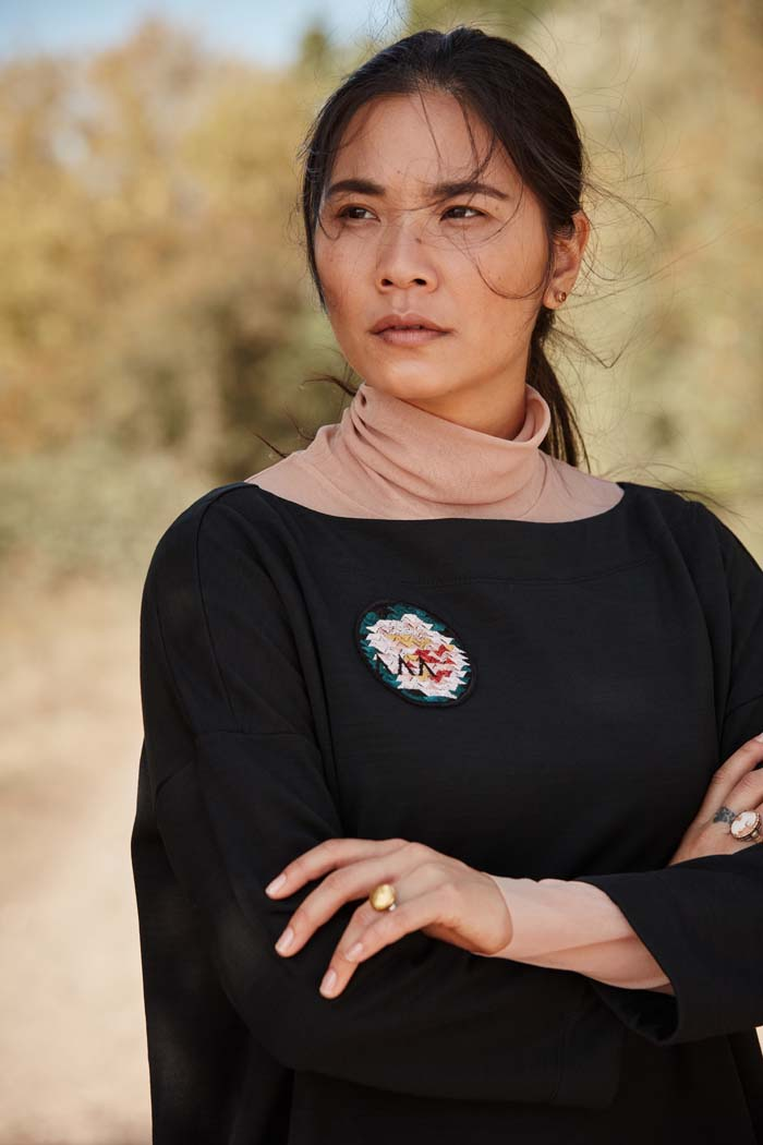 Woman wearing the Asmuss Oversized Boat Neck Sweat in black with embroidered rose badge. Stylish, sustainable lifestyle womenswear for any of your everyday adventures whether they are everyday or when you are travelling