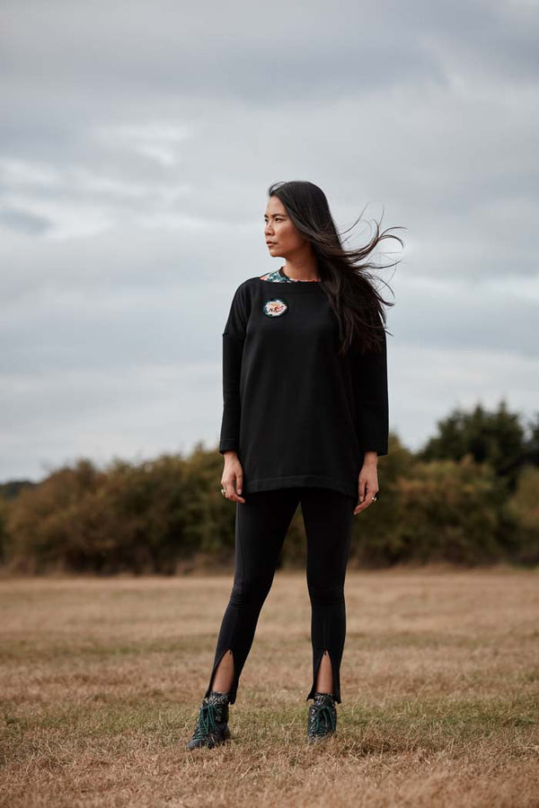 Woman wearing the Asmuss Oversized Boat Neck Sweat with embroidered rose badge. The perfect elevated sweatshirt to throw on over practically anything including activewear for all of your everyday adventures..