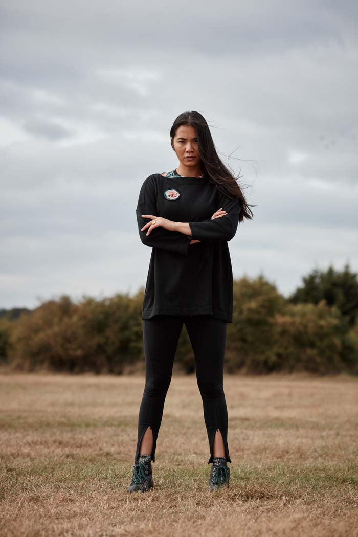 Woman standing with arms crossed in a fieldwearing the Asmuss Twisted Leggings with zip detail on lower front leg, pocket in front waistband and drawstring to keep them snug. Made in the UK from recycled nylon and elastane for 4 way stretch. Sustainable activewear that looks great on for all your everyday adventures including lazing on the couch or out running.
