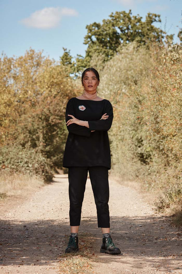 Woman wearing the Asmuss Panelled Trousers on a walk in the outdoors. The Panelled Trousers are made with sustainable EVO fabric that has stretch and water resistance. The Panelled Trousers feature 3 zipped pockets for style and comfort on your everyday adventures whether at home or in the outdoors.