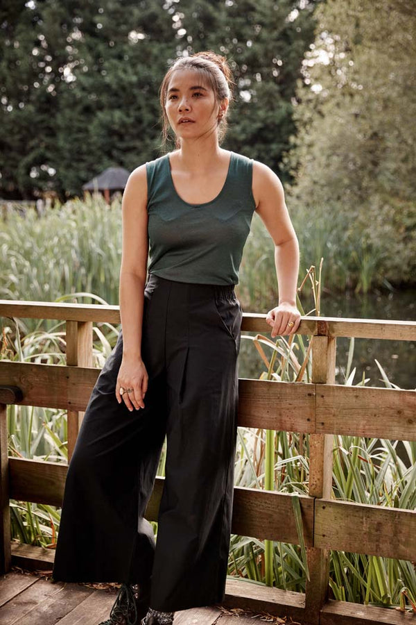 Woman, leaning against a wooden railing near a pond, wearing the Asmuss Wide Leg Trouser in black. Made in the UK in small batches from a sustainable fabric with built in stretch and water resistance. Stylish, sustainable trousers that are elevated by the design details including hidden zip pocket and high elasticated waist for convenience and comfort. Perfect for all your everyday or travel adventures.