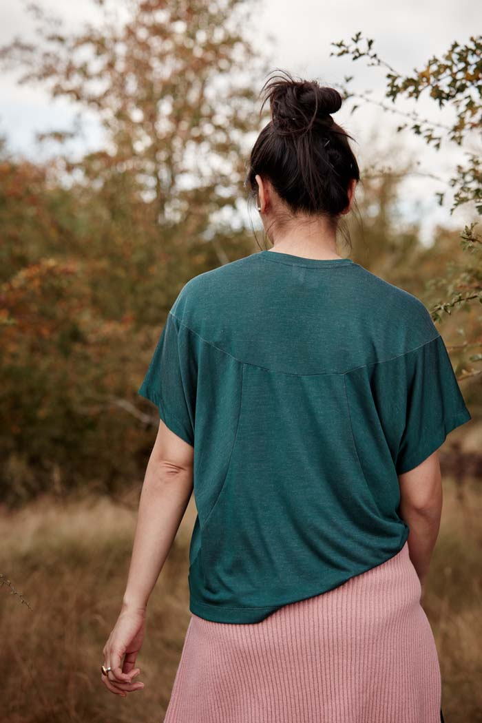 Back view of woman in the outdoors wearing the Asmuss Panelled T-shirt in Pine Green. Made from a sustainable fabric that feels luxurious and drapes. A t-shirt elevated with interesting detailing. A great stylish and sustainable luxury t-shirt that is the perfect activewear t-shirt that can be worn on your everyday adventures.