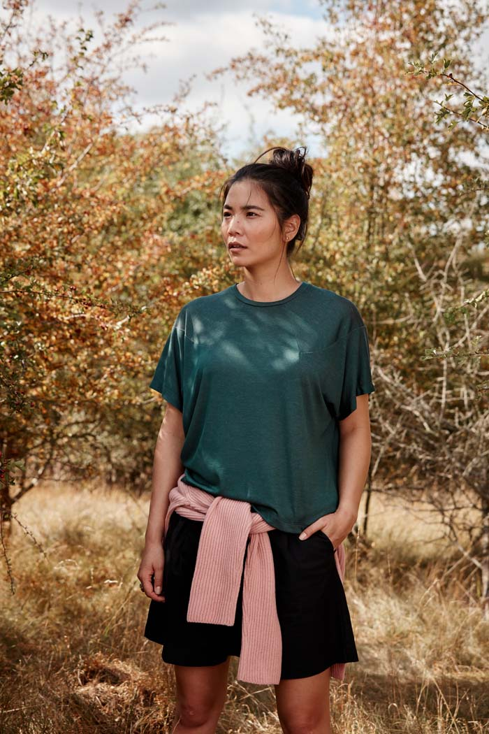 Woman in the outdoors wearing the Asmuss Panelled T-shirt in Pine Green. Made from a sustainable fabric that feels luxurious and drapes. A t-shirt elevated with interesting detailing. A great stylish and sustainable luxury t-shirt that is the perfect activewear t-shirt that can be worn on your everyday adventures.