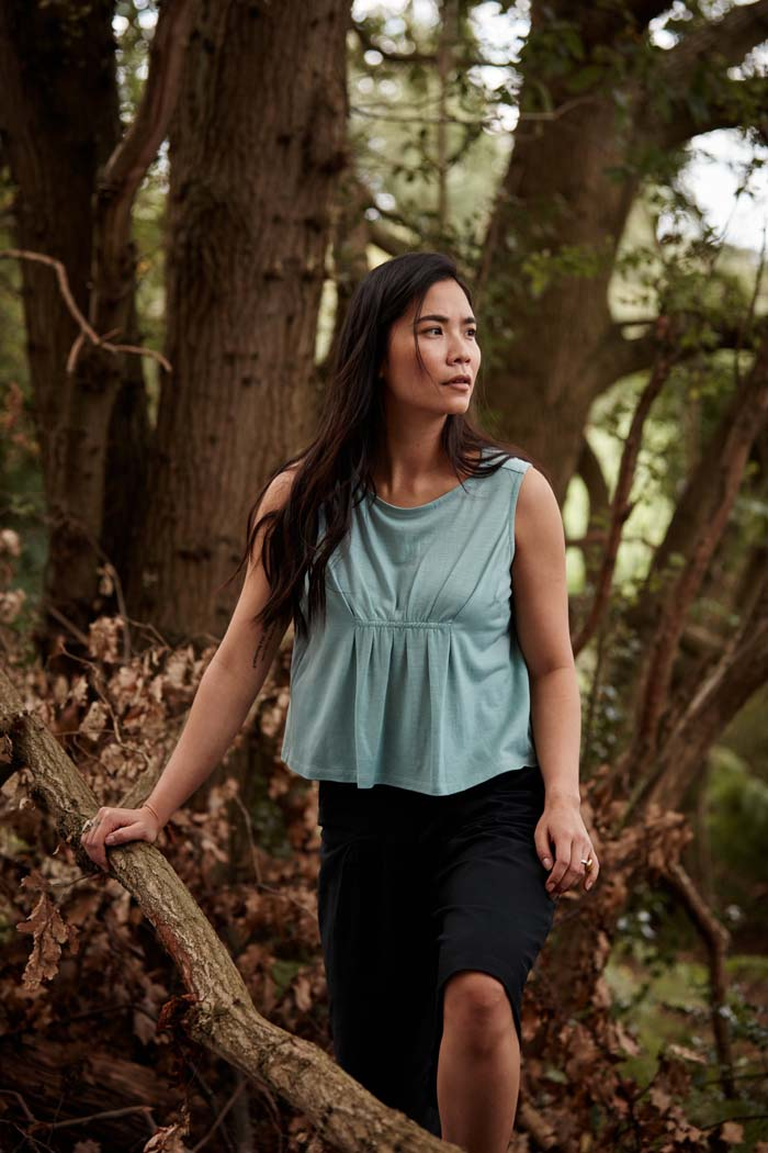 Woman wearing the Asmuss Pleated Tank in sea green while exploring a forest. Made in the UK from a blend of wool and 37.5 technology to help keep your ideal body temperature so it is perfect for travelling with or wearing at home or office. The pleat detail and darts to prevent gaping make it a great elevated essential for all your everyday adventures.