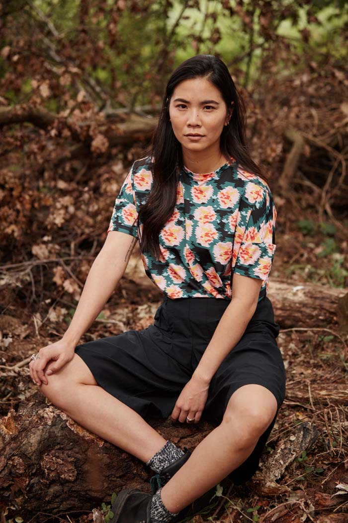 Woman sittting in woods wearing the Asmuss Rose Print T-shirt a great activewear or casual wear top. Stylish and sustainable lifestyle womenswear for your everyday adventures.