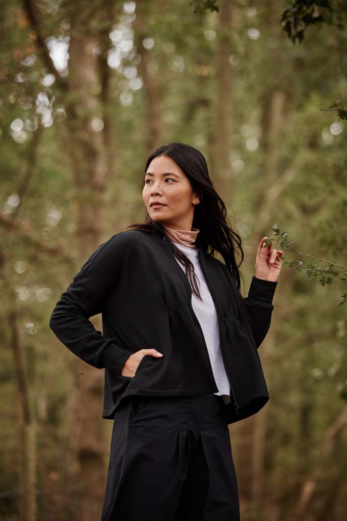 Woman, in the woods, wearing the Asmuss Pleated Zip Through Sweat with pleats and invisible pocket detailing. Stylish, sustainable lifestyle womenswear for when you want to feel cosy. A great elevate essential for all your everyday adventures.