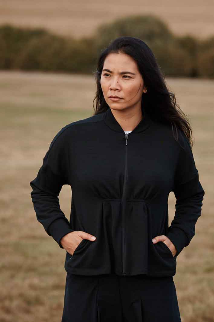 Women wearing the Asmuss Pleated Zip Through Sweat with pleats and invisible pocket detailing. Stylish, sustainable lifestyle womenswear for when you want to feel cosy. A great elevate essential for all your everyday adventures.