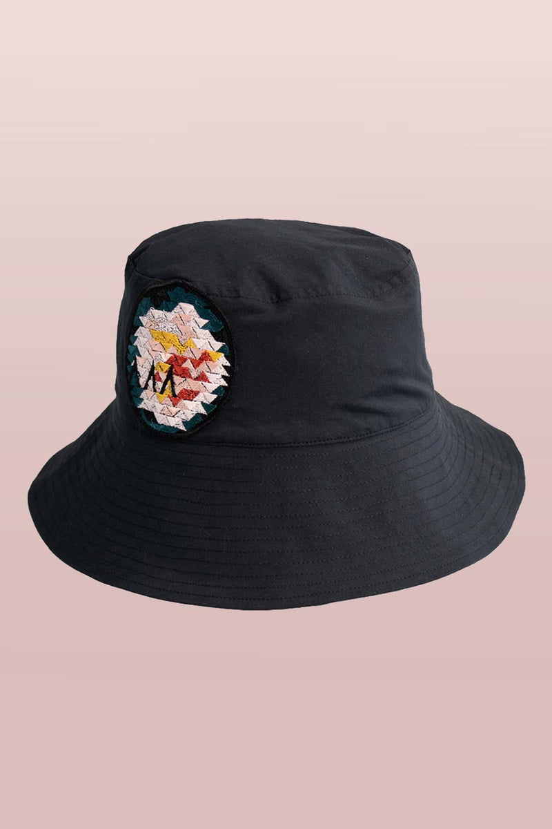 Front view of the Asmuss Wide Brim Bucket Hat in black with rose embroidery badge. The perfect sun hat to keep the sun off your face but still look good and with water resistance to keep the rain off too.