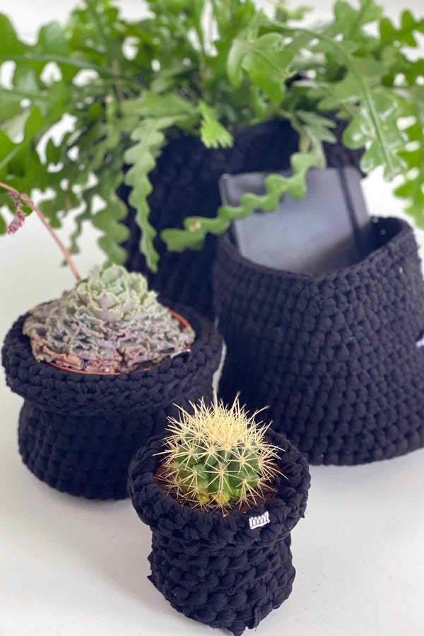 Collection of Asmuss Limited Edition hand crocheted baskets in black from upcycled materials. Perfect to cover plant pots or for your working from office.