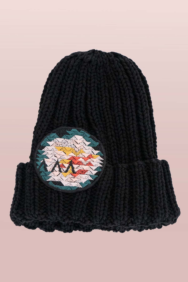 Asmuss Limited Edition Hand Knitted Beanie in Black with Geometric Rose Embroidered Badge to elevate your winter essential. It is made from yarn that would have gone to waste so it is it truely sustainable.