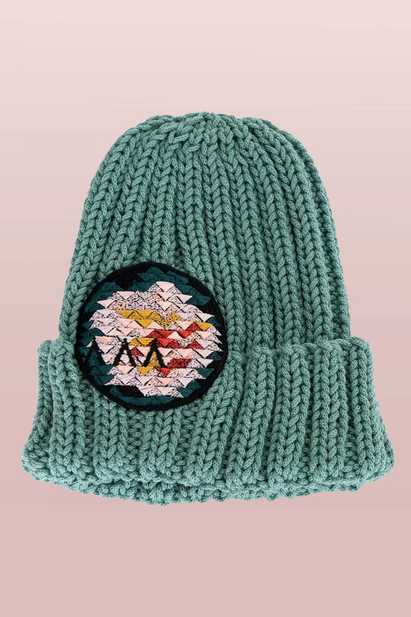 Asmuss Limited Edition Hand Knitted Beanie in Sea Green with Geometric Rose Embroidered Badge to elevate your winter essential. It is made from yarn that would have gone to waste so it is it truely sustainable.