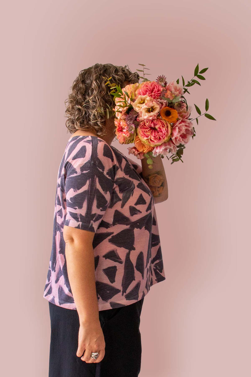 Asmuss Black Rose A-line T-shirt side view showing slim sleeve and print detailing while model holds a bunch of flowers in front of her face